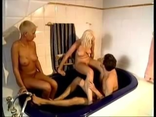 2 Blonde German lesbians are toying in a bathtube, when, oh surprise !, a guy...