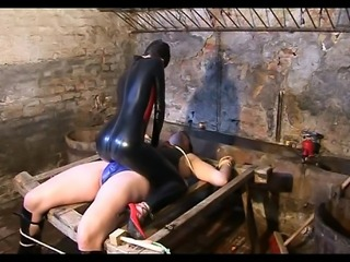 Two delicious dominas in latex outfits whipping their slaves body