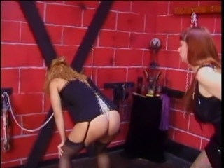 Collared and shackled blonde bends over for dominatrix spanking