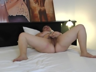 Fat ass matured maiden in bra stripteasing seductively on bed