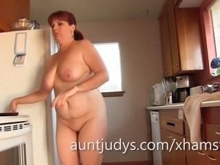 Mature Cinna Page gets naked in the kitchen.