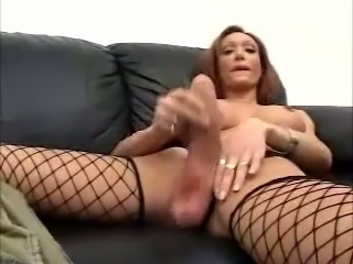 Tranny in Fishnet Stockings Jerking Off Her Big Cock