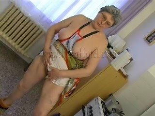 Hot granny Gerlinde washes the dishes naked, wearing only a kitchen gown. She...