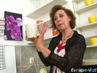 Older mature granny making coffee and playing seductively in old kitchen