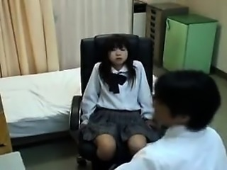 Schoolgirl patient sits in the chair while he gets her nake