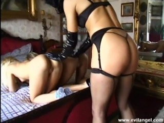Lesbians fisting and fucking with strap on in a threesome scene