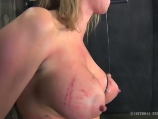 Busty blonde with tattoos is having a hard time in the dungeon